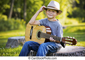 portrait of a little boy with guitar - cuacasian boy with...