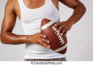Black man with american football - Black man holding an...