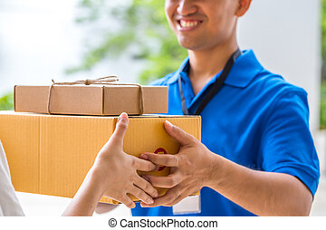 Woman accepting a delivery of cardboard boxes from...
