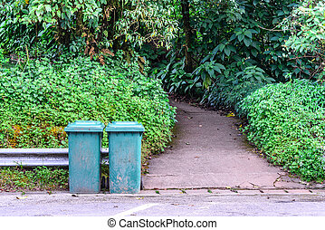 Green trashcan for keeping garbage in public park.