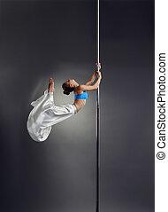 Studio photo of petite woman dancing on pole
