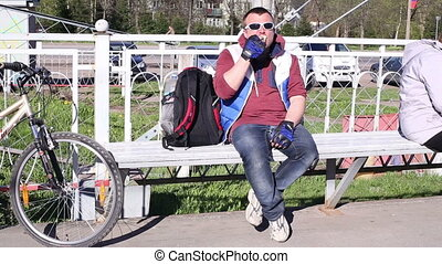 Man in sunglasses eating ice cream on a bench