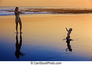 Mother with little child on the sunset sea beach -...
