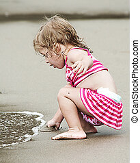 child at the seaside - child playing with the sea waves