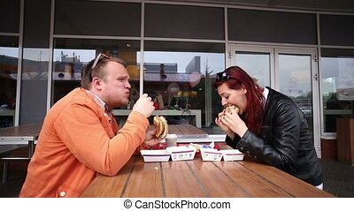 Woman and man eating burger in a fast food