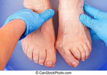 Foot care - Doctor hand examining an elderly patients foot