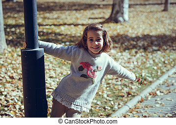 Little girl playing in a city park in autumn, wearing pants...