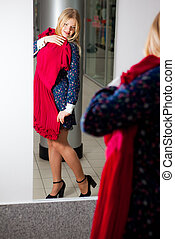 Woman trying red dress shopping for clothing. Beautiful...