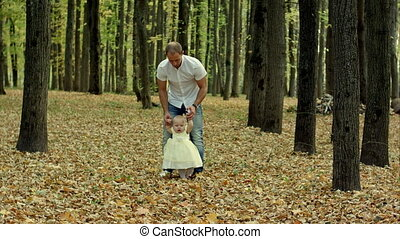 Happy smiling baby held up by her father in autumn park