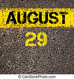 29 August calendar day over road marking yellow paint line -...