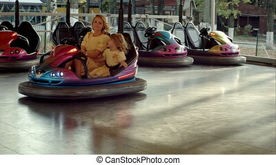 Young mother with her daughter drive on bumper cars. Shot on...
