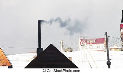 The smoke from the chimney of the house.