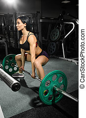 Brunette strong fitness sexy woman doing barbell squats in a...