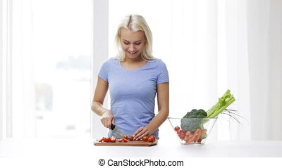smiling young woman chopping tomatoes at home - healthy...