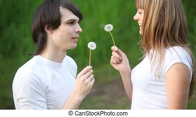 young man and girl blowing flowers, facing each other