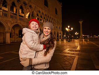 Mother and child standing on Piazza San Marco in the evening...