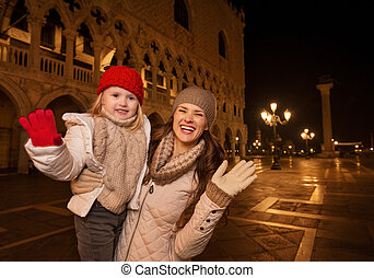 Mother and child handwaving on Piazza San Marco in the...