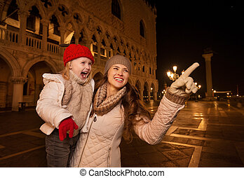 Mother pointing on something to child on Piazza San Marco -...
