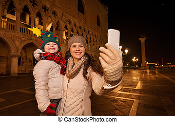 Mother with child taking selfie on Piazza San Marco in...