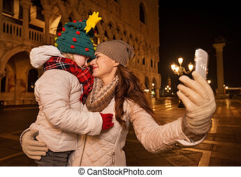 Mother and child hugging while taking selfie on Piazza San...