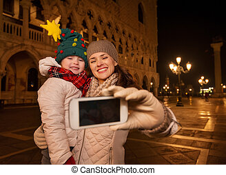 Mother and child taking selfie on Piazza San Marco in Venice...