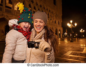 Mother and child looking on photos on Piazza San Marco in...