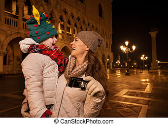 Happy mother with camera and child on Piazza San Marco in...