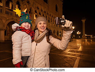 Happy mother and child taking photos on Piazza San Marco,...