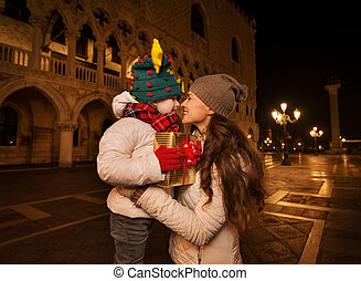 Happy mother hugging child with Christmas gift box in Venice...