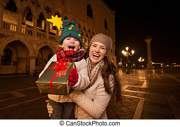 Happy mother and child showing Christmas gift box in Venice...