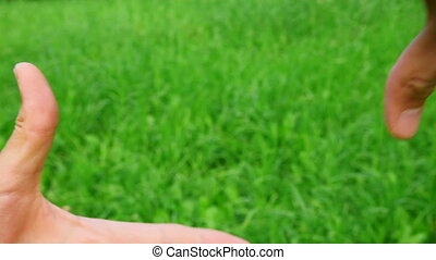hands border on green grass background