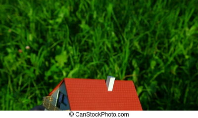 toy house on palm on green grass background
