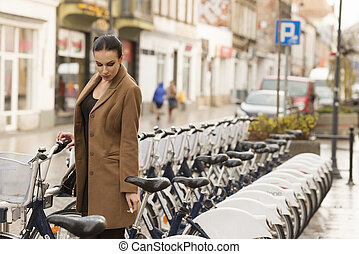 winter dressed woman near city bike - young woman standing...