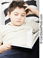 Boy reading book closeup - Caucasian boy reading book while...
