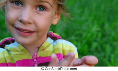 little girl talking on green grass background
