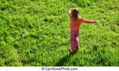 little girl running around on green grass