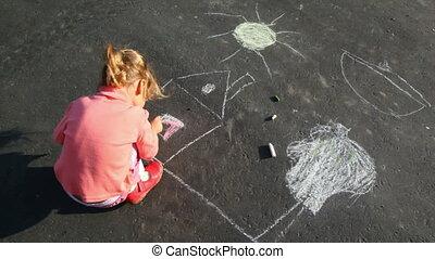 little girl chalking on asphalt
