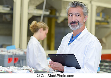 Man in white coat holding clipboard