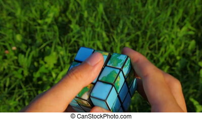men solves rubik\'s cube on green grass background