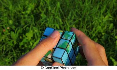 men solves rubik\'s cube on green grass background