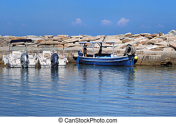 blue boat on blue sea - blue boat moored to a seawall on...