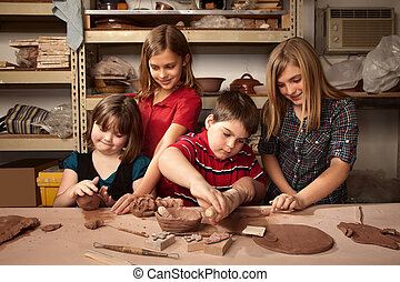 Children in a clay studio - Four children working on crafts...