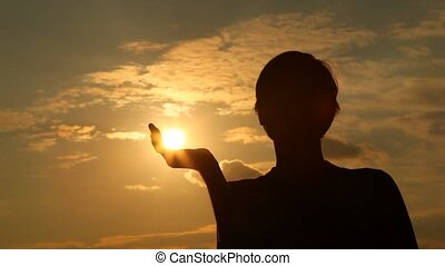 Silhouette of man which has taken away sun in hand