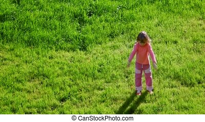 little girl waving hands and jumping on green grass