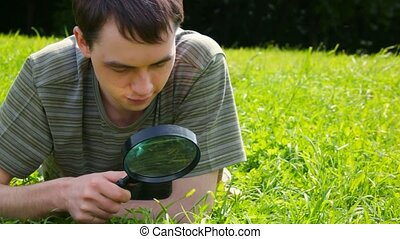 young men looks through a magnifying glass