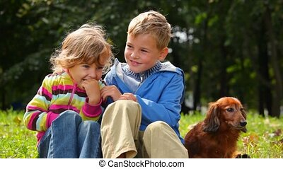 boy and girl with dog sitting on grass