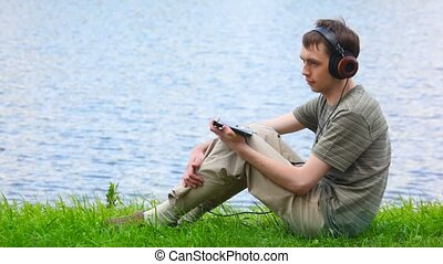 young men listen music in headphone on water background