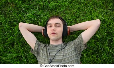 young men listen music in headphone lying on green grass