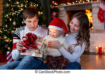 Happy family opening Christmas gift sitting in living room