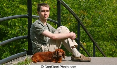 young men stroking dog